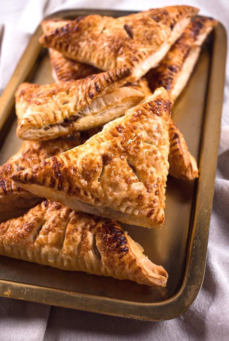 Turnovers baked and stacked on a baking sheet