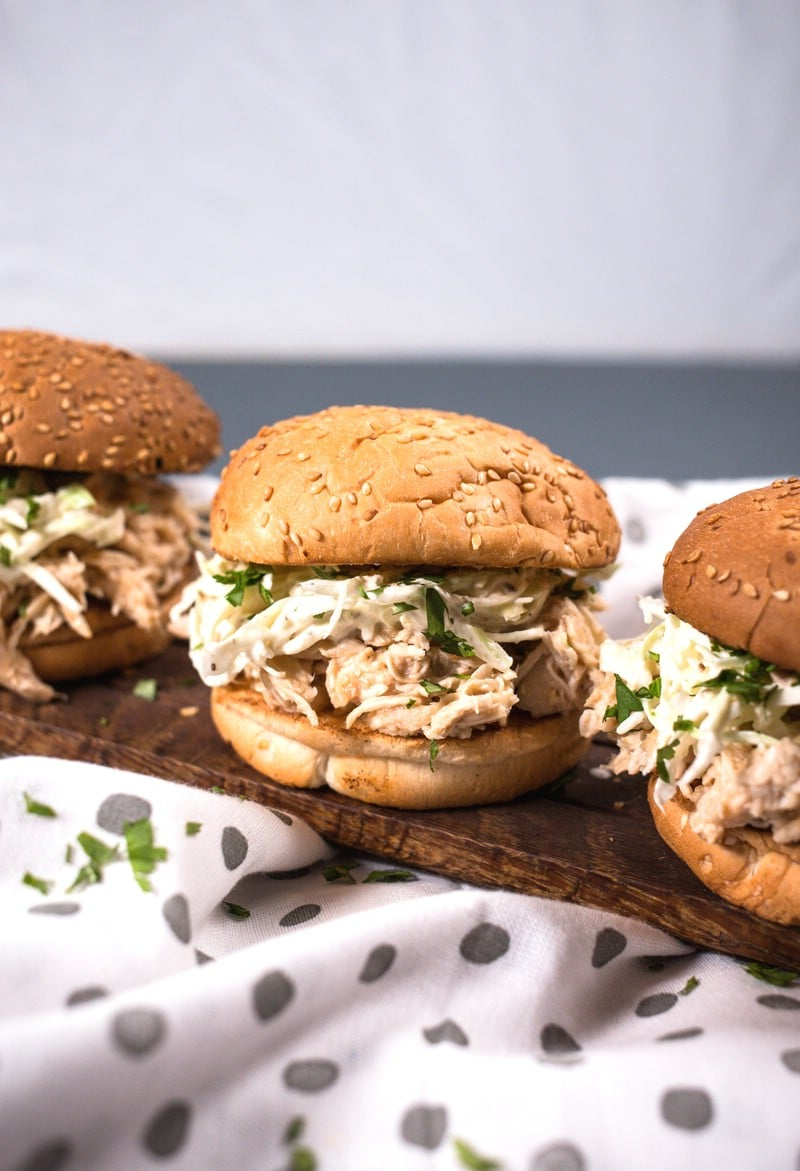 A trio of pulled chicken sandwiches on a wooden board with coleslaw