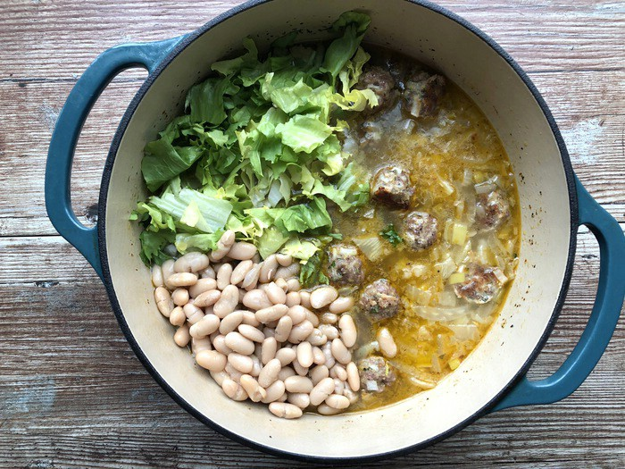 Adding in beans and escarole to wedding soup