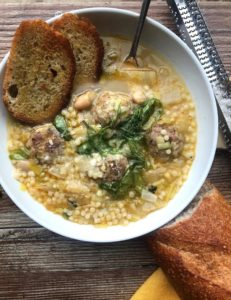 Bowl of Italian wedding soup with bread