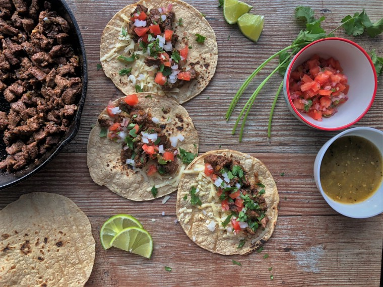Overhead picture of corn tortillas topped with carne asada and pico de gallo
