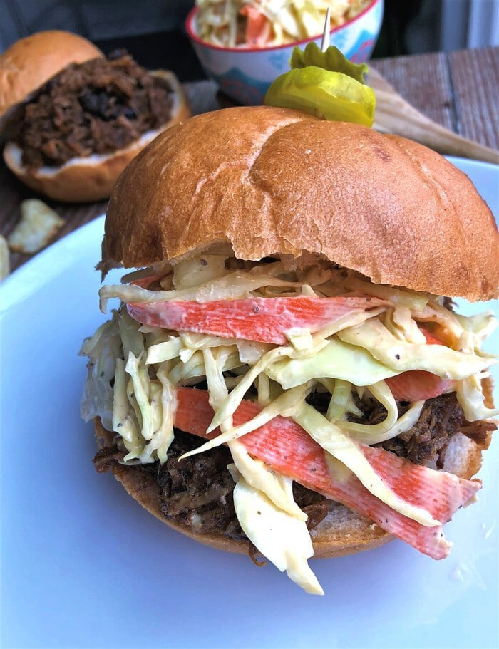 Pulled pork sandwich with creamy cole slaw on white plate