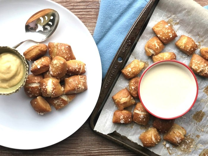 Pretzel bites with queso and dip on a white plate