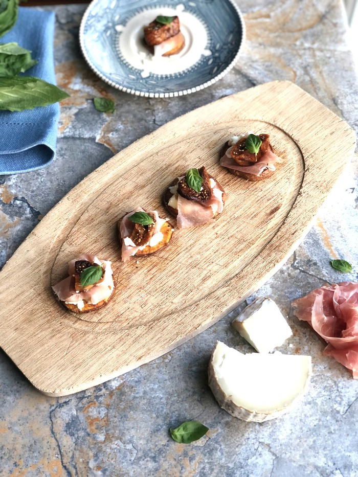 Wood platter topped with crostini