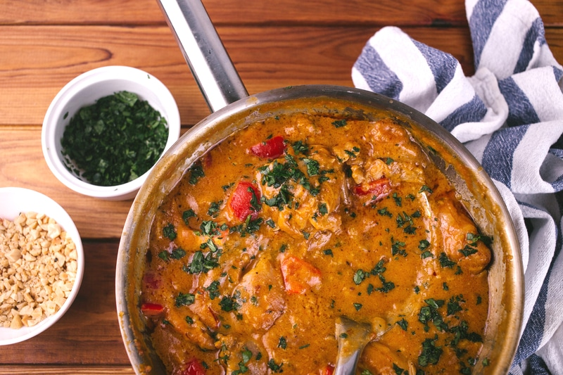 Skillet of chicken curry on table