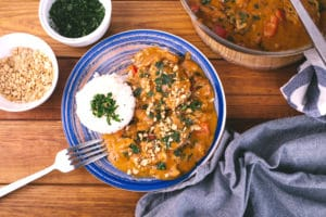 Blue plate with chicken curry topped with cilantro and peanuts