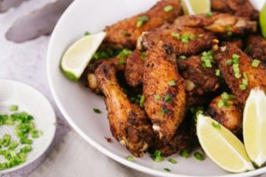 Salt and pepper chicken wings on white plate with lime wedge