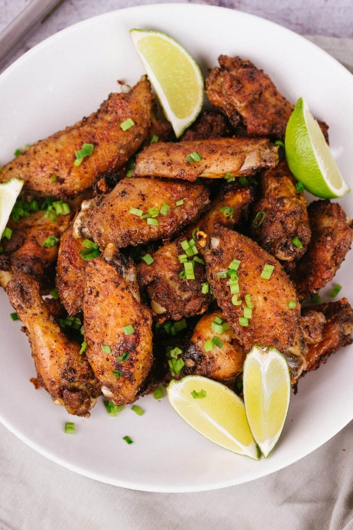 Bowl of baked chicken wings with lime wedges