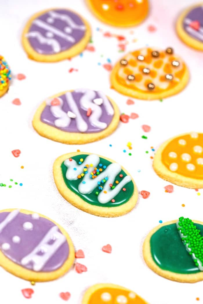 Purple and green iced sugar cookies on white table