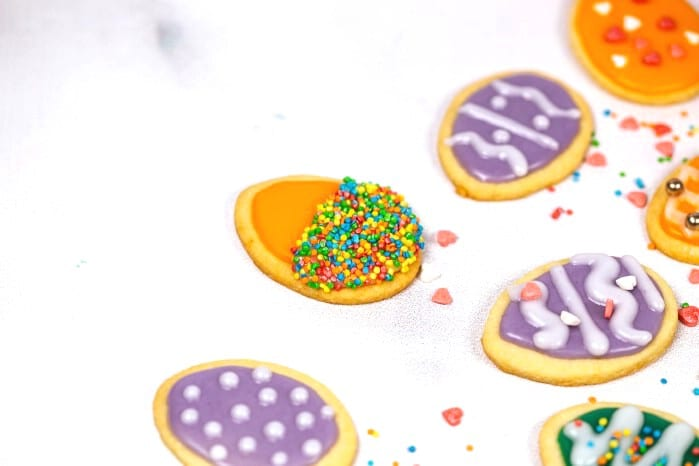 Orange iced cookies with sprinkles on white surface