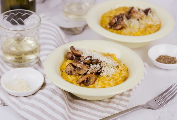 Risotto in bowl by glass of wine