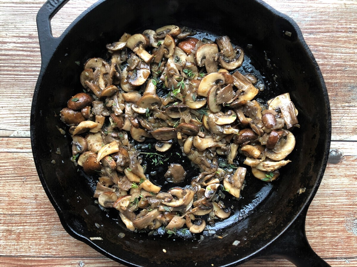 Cooked mushrooms and herbs in cast iron skillet