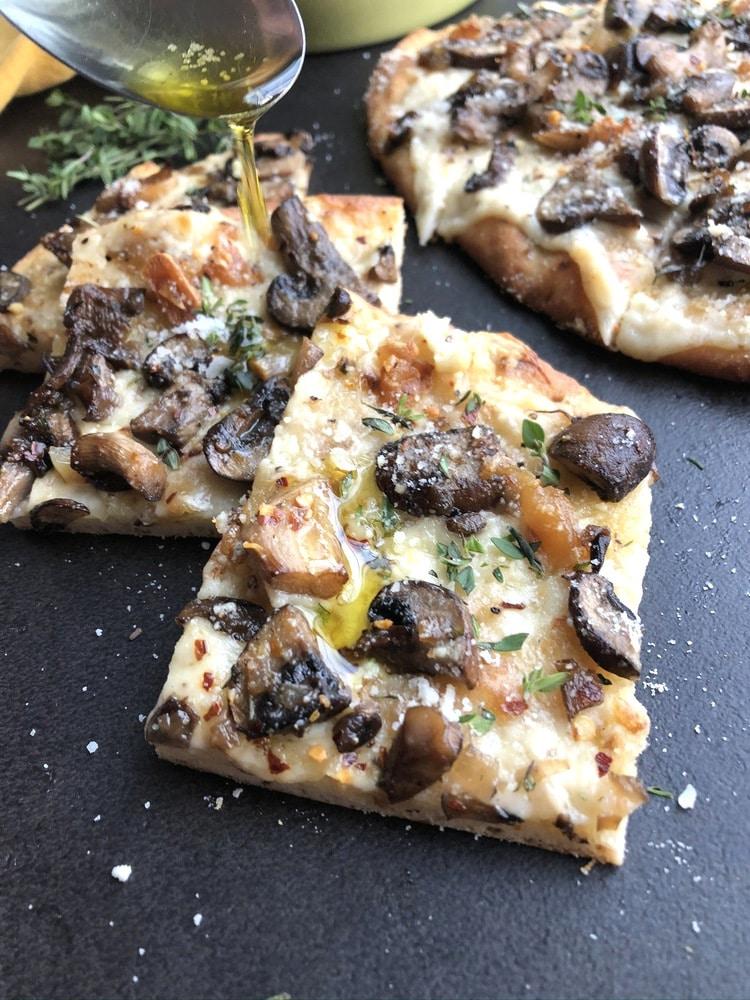 Slices of mushroom naan pizza on black table