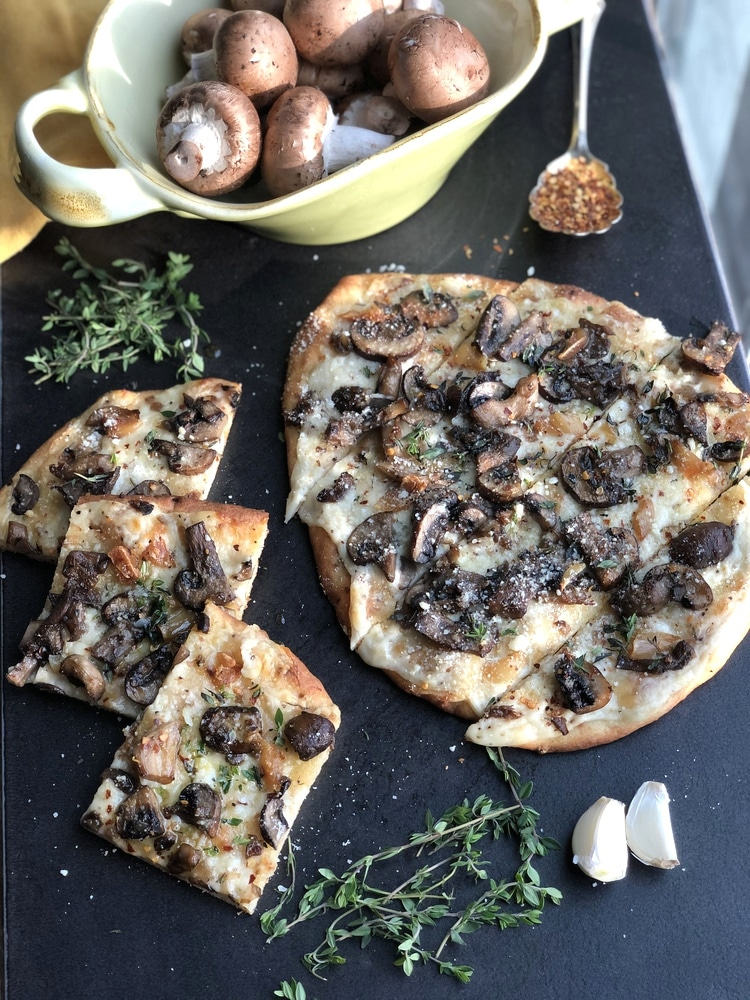 Bowl of mushrooms by naan pizza