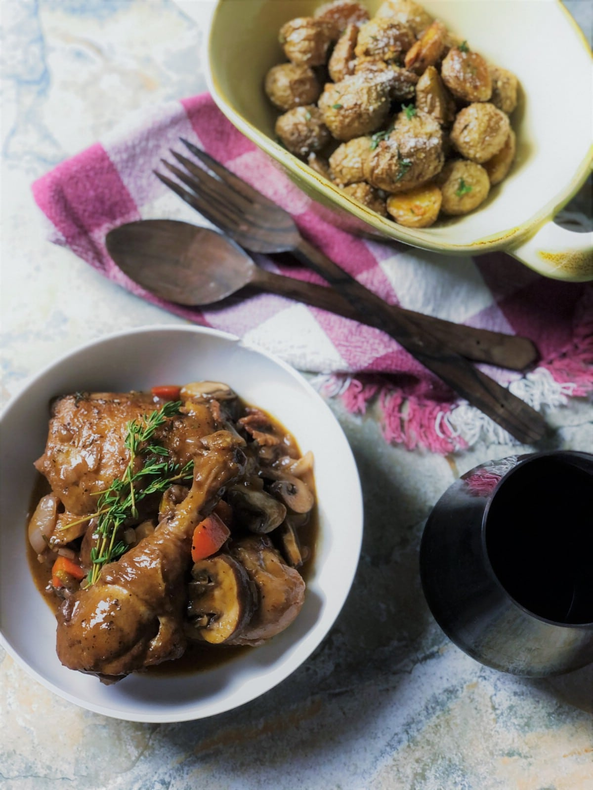 Coq au vin in white bowl next to roasted potato
