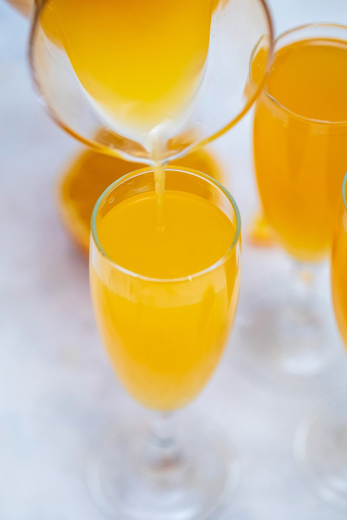 Adding orange juice to champagne flute