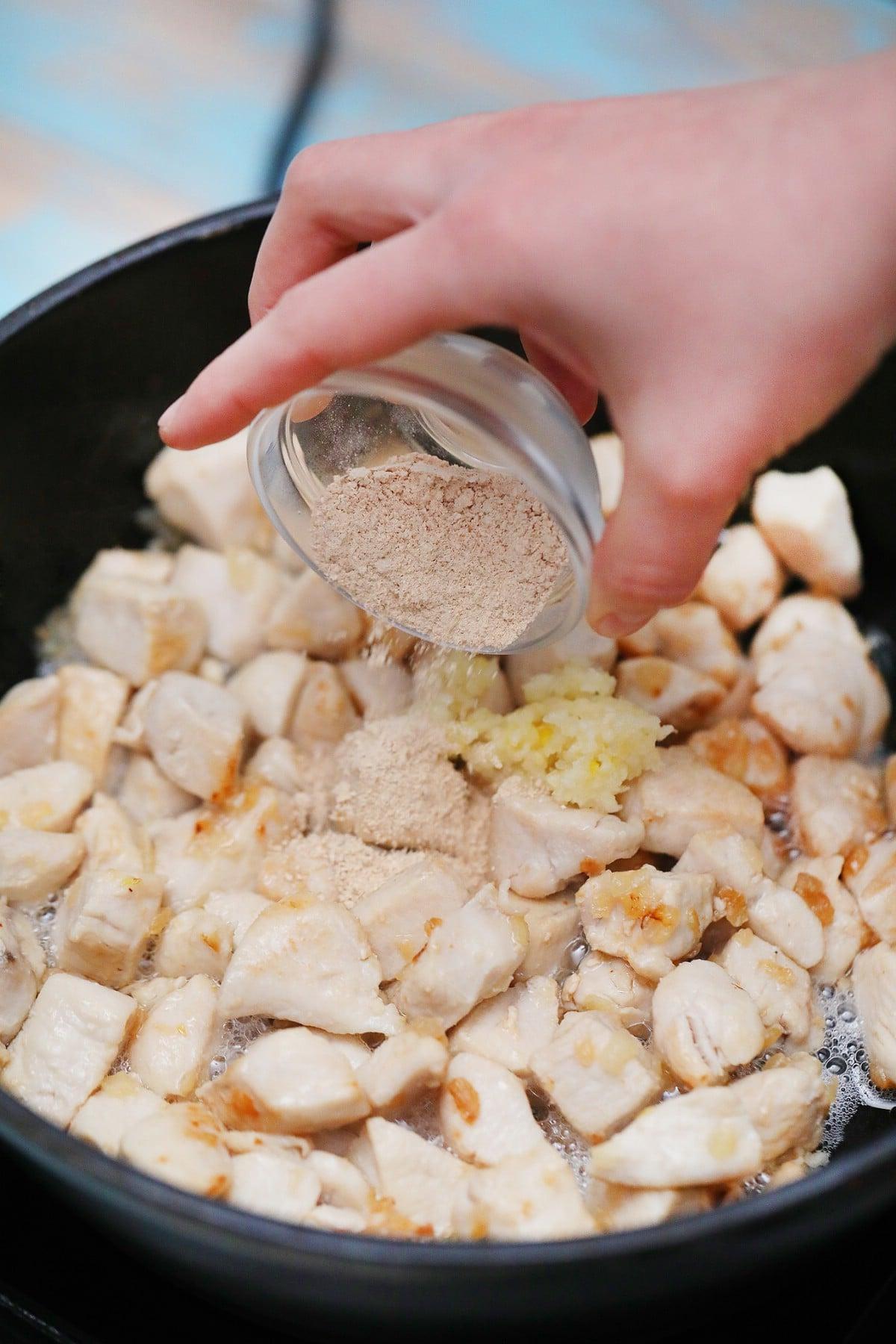 Adding spices to chicken