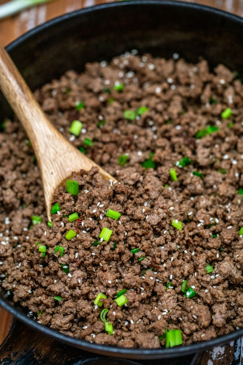 Ground beef and green onions being cooked in cast iron skillet