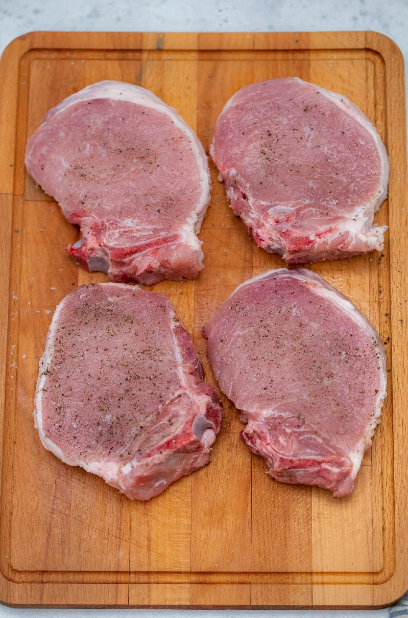 Raw pork chops on cutting board