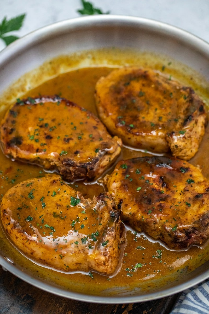 Cooked pork chops in skillet with sauce