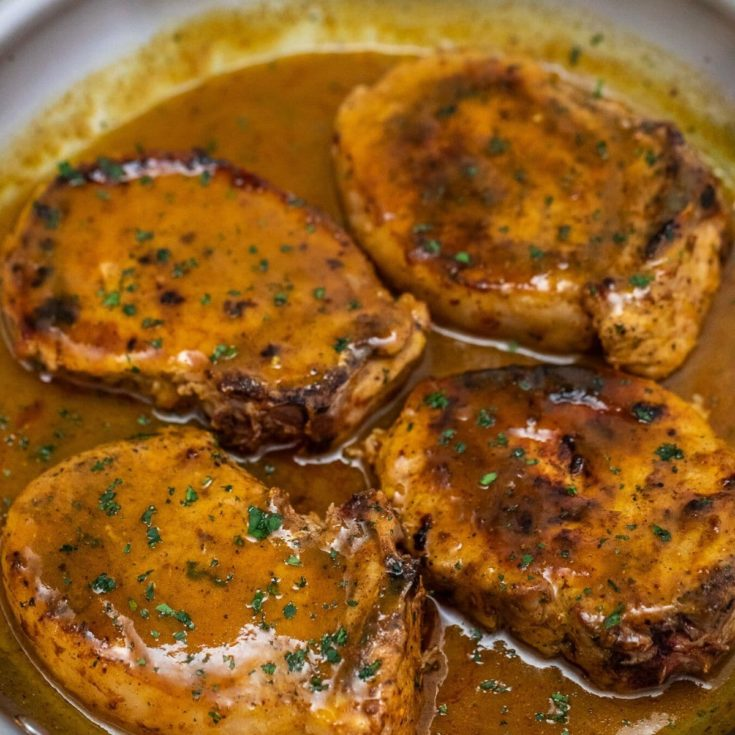 Pork chops in skillet covered in sauce