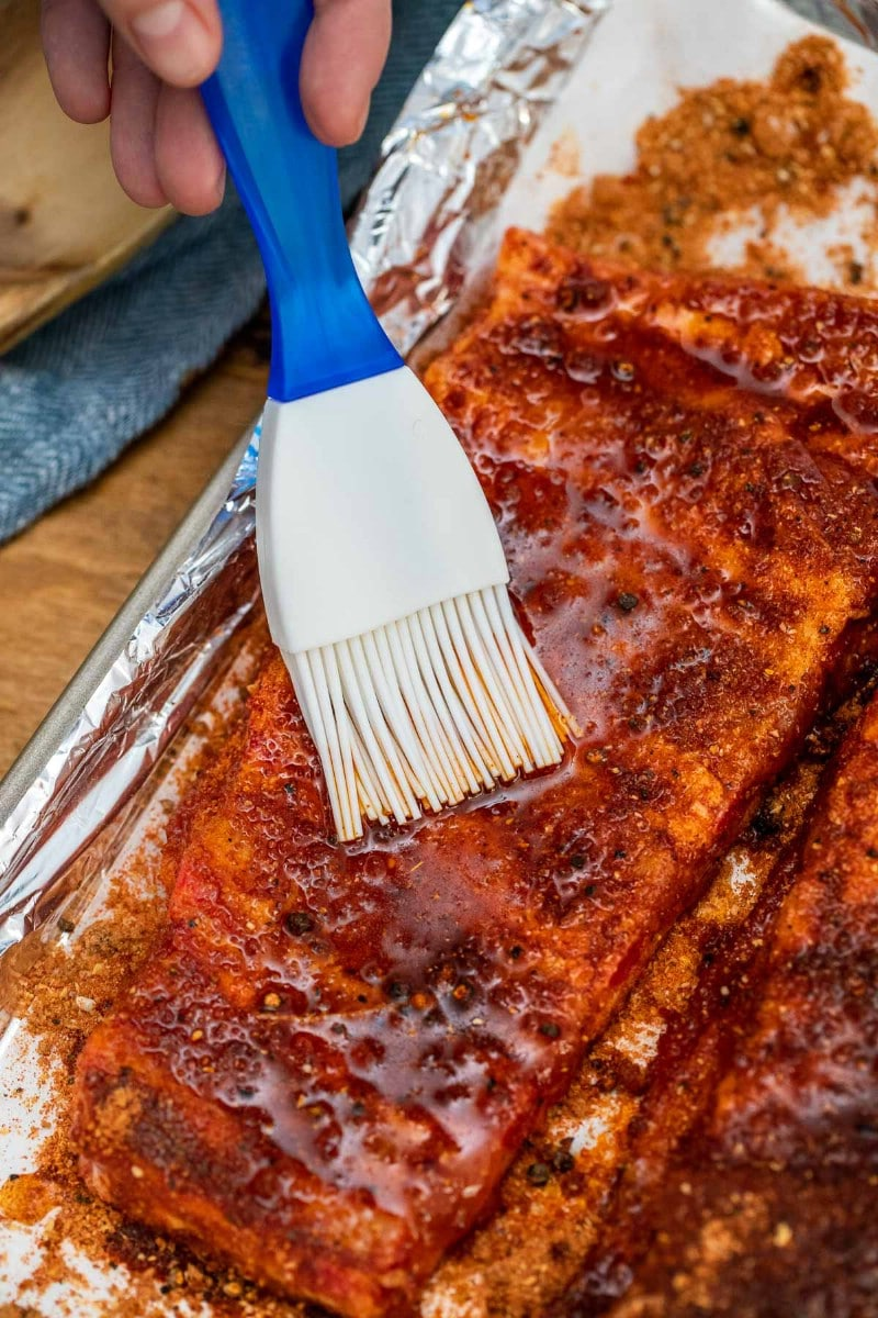 Brushing ribs with sauce
