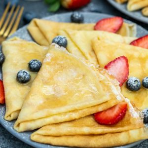 Crepes on a blue plate with berries