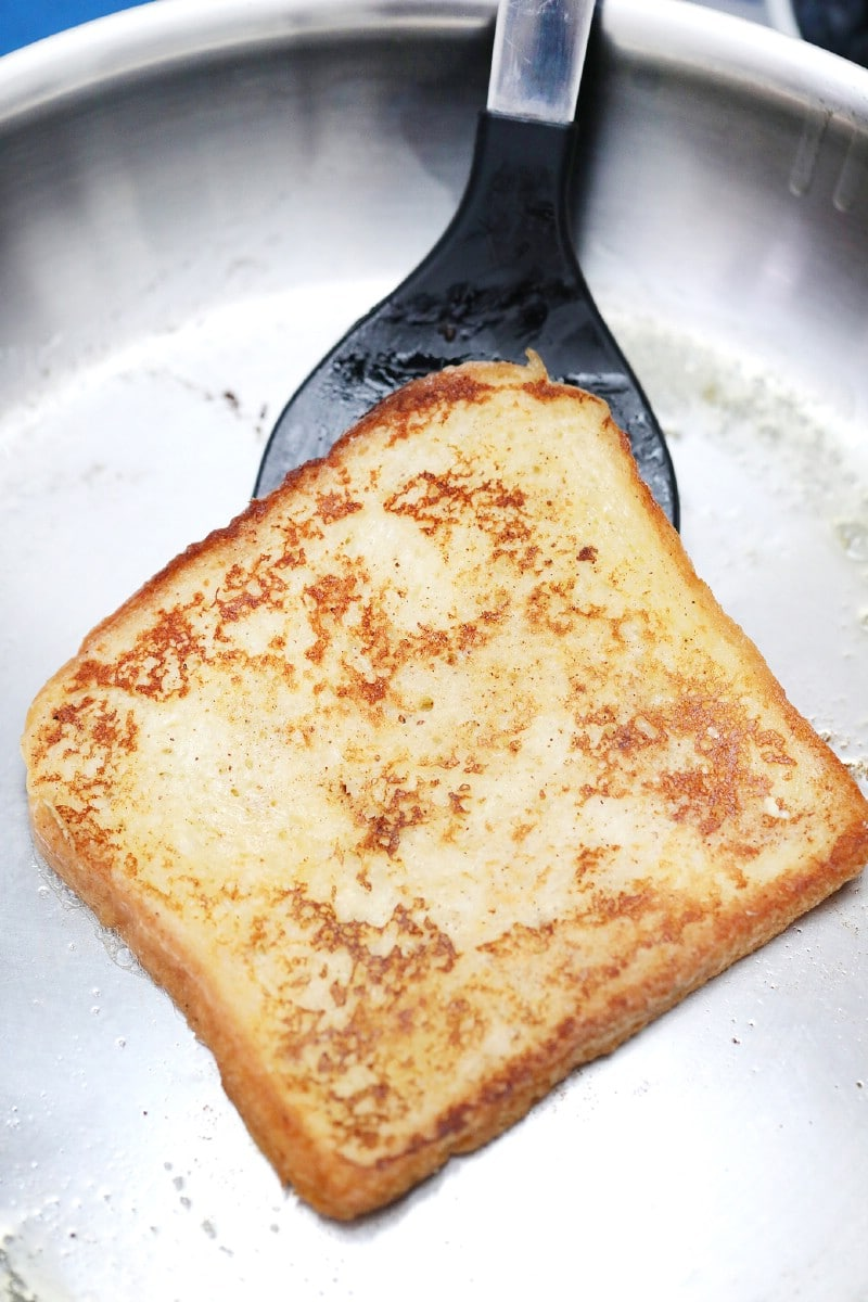 Spatula holding toast in skillet