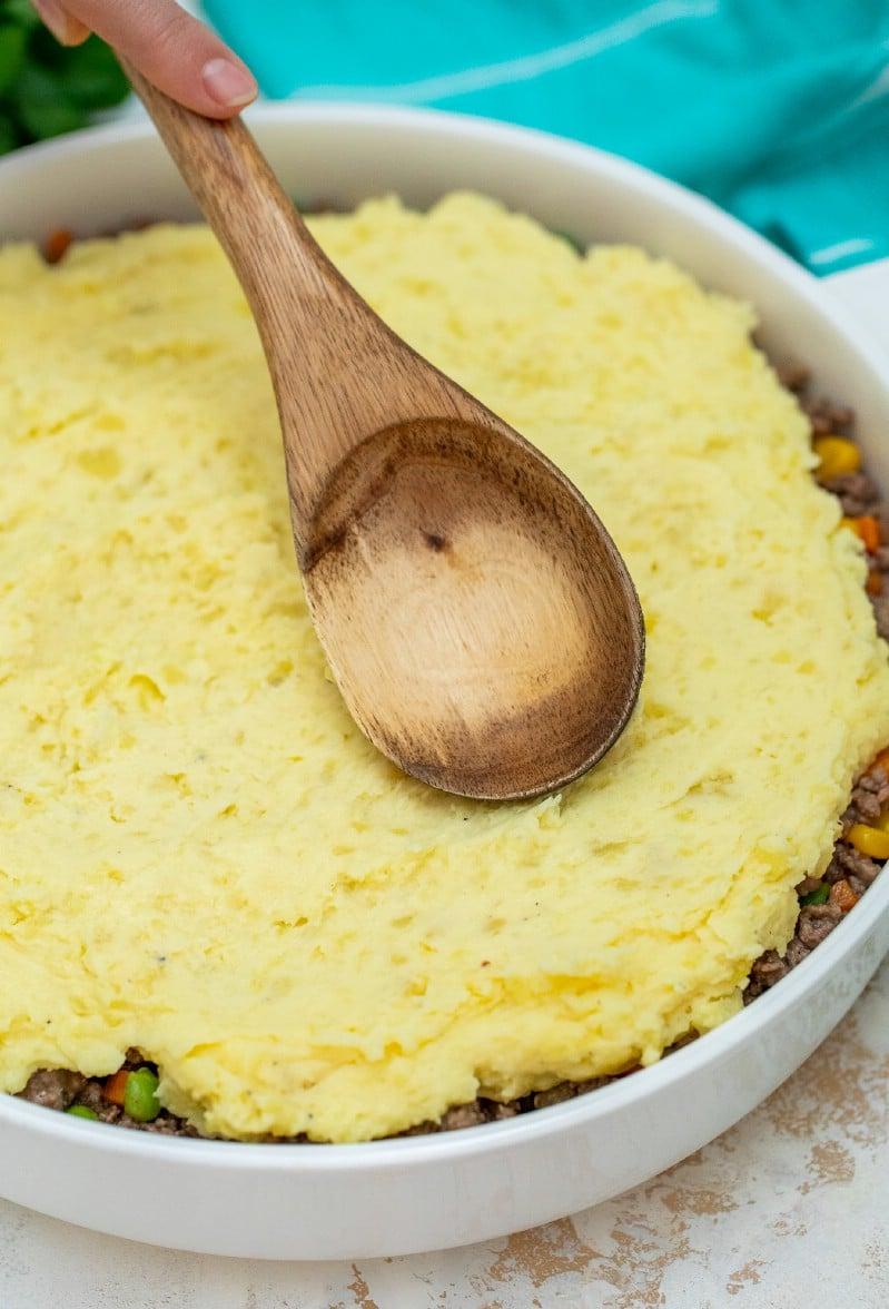 Spreading potatoes over shepherds pie