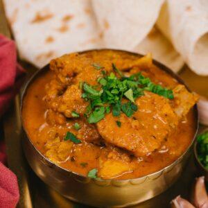 Chicken curry in brass bowl