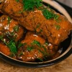 Beef rouladen in black bowl with handle