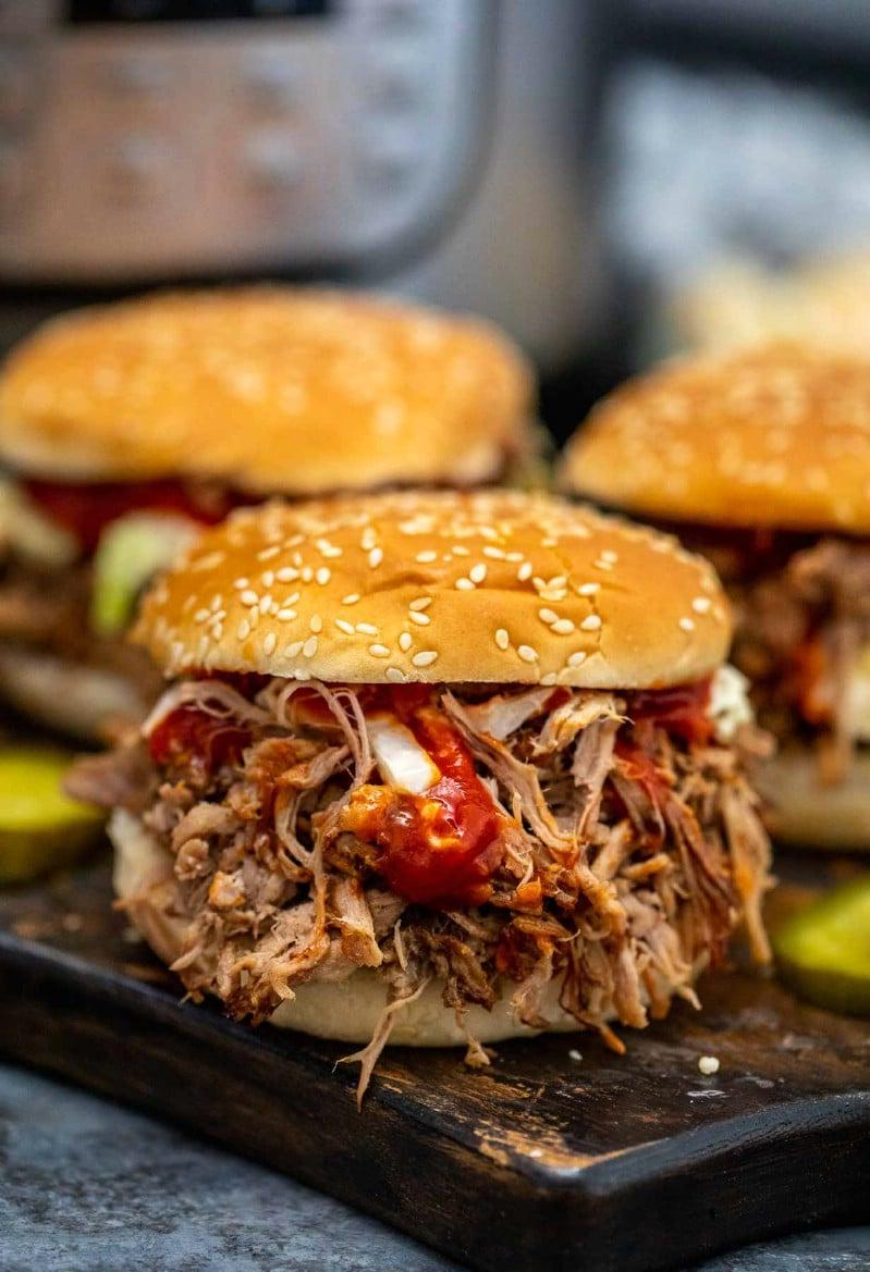 Pulled pork on sesame seed bun on black plate