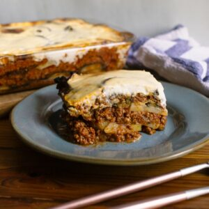 Beef moussaka casserole slice on teal plate