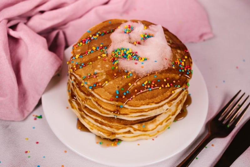 Stack of pancakes on white plate with pink napkin