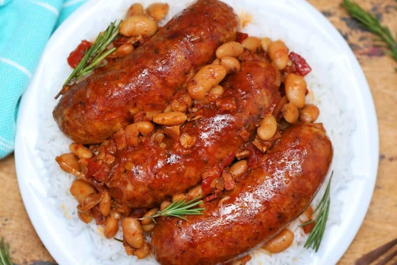 Pork sausage and beans on white plate