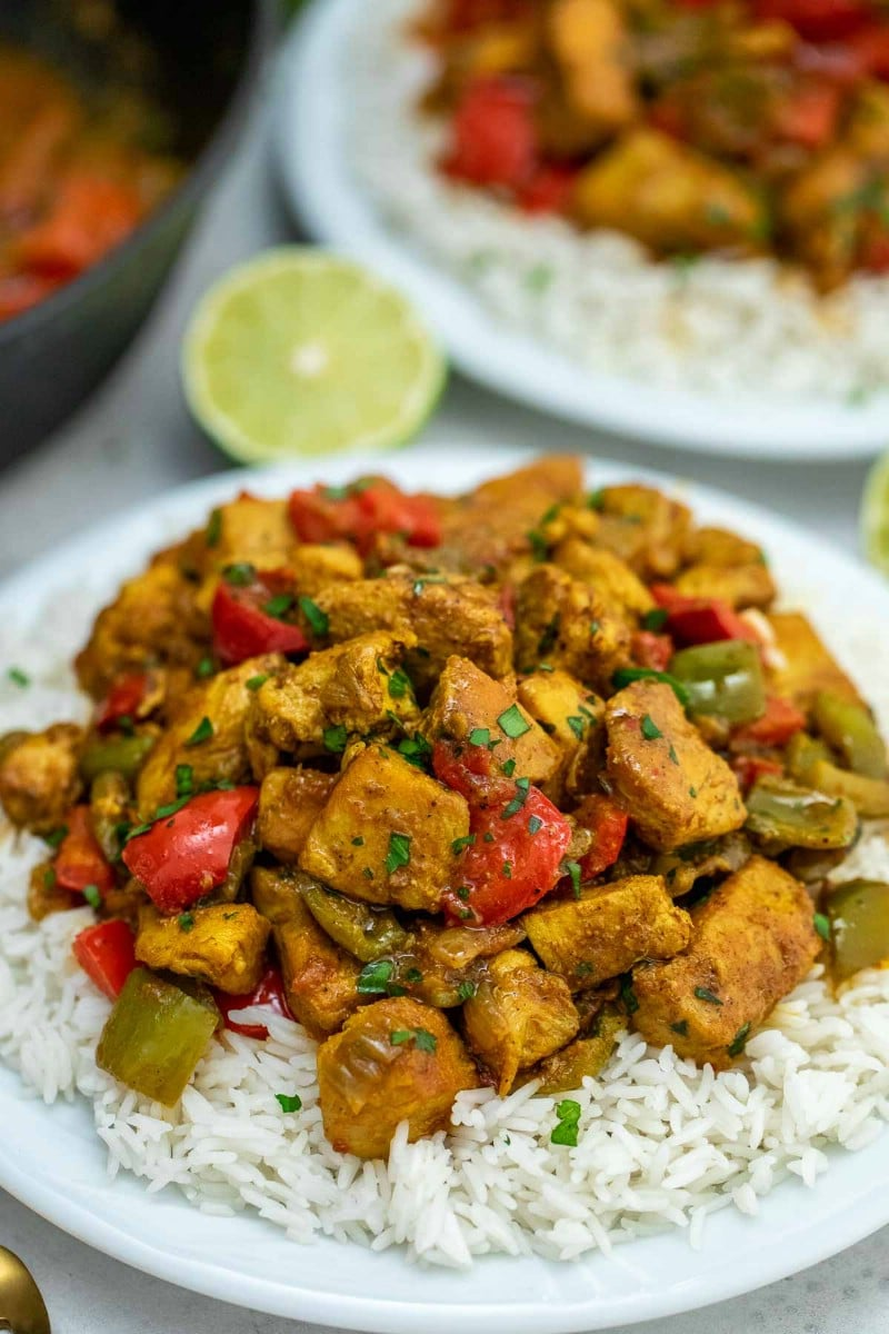 Jamaican chicken curry on white plate with rice