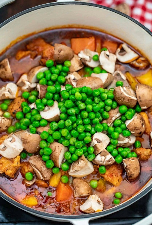 Adding mushrooms and peas to pork stew