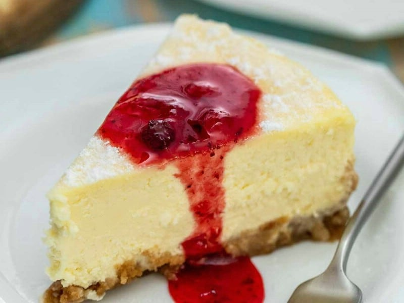Slice of cheesecake on white plate with strawberry sauce