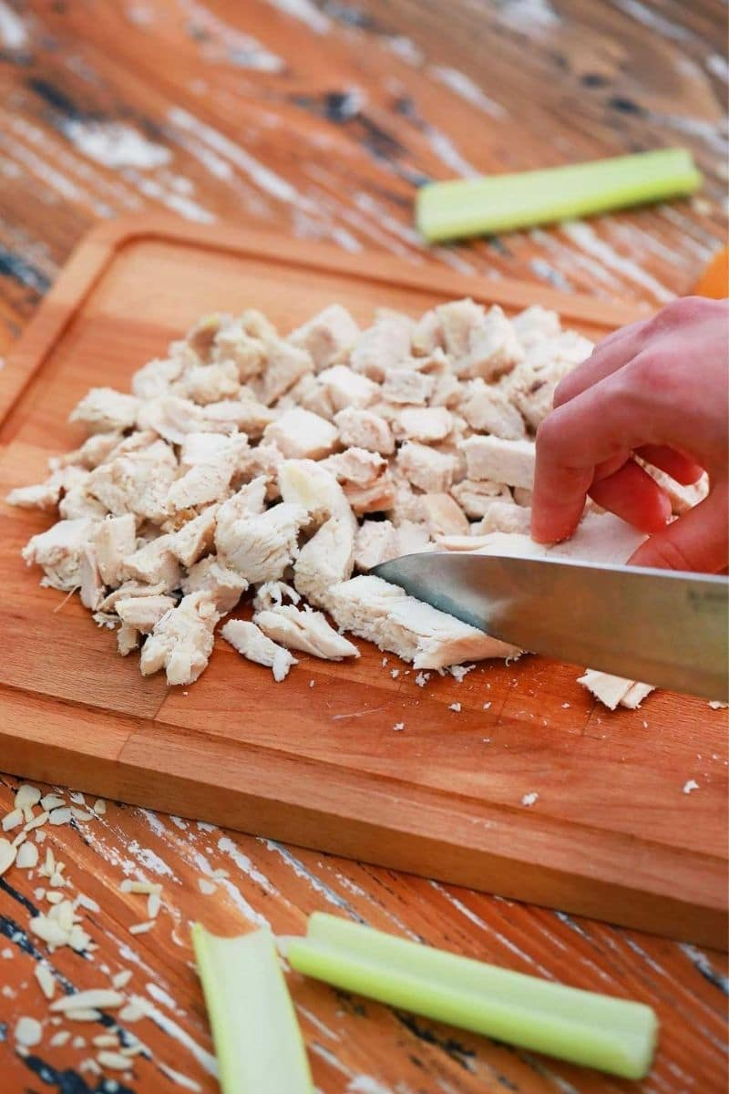 Chicken being cut on cutting board