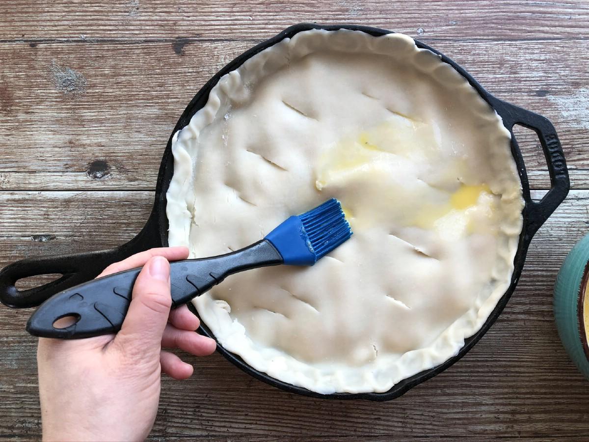 Brushing egg wash onto crust