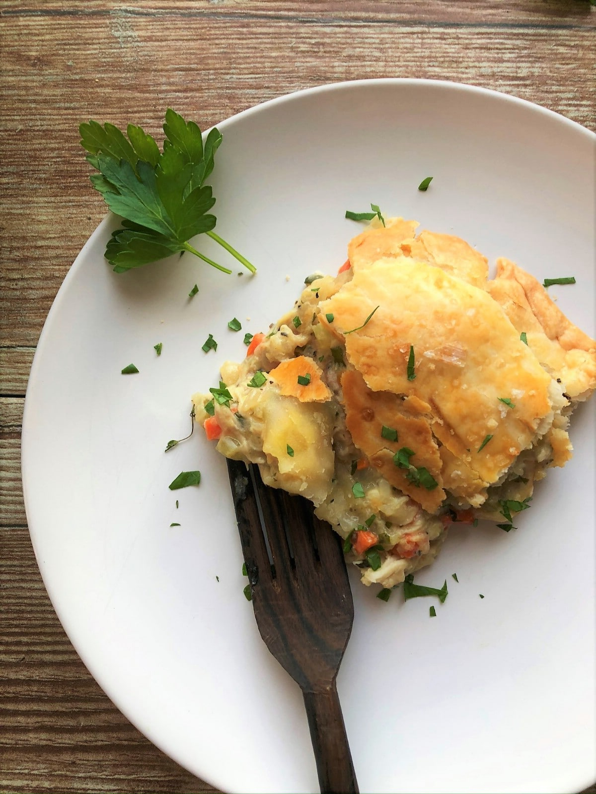 Chicken pot pie with herbs on white plate