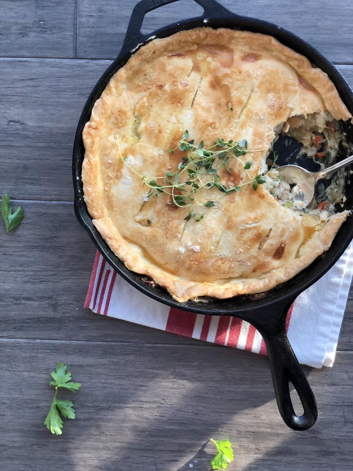 Spoon in skillet of chicken pot pie