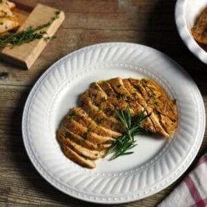 Sliced garlic chicken on white plate