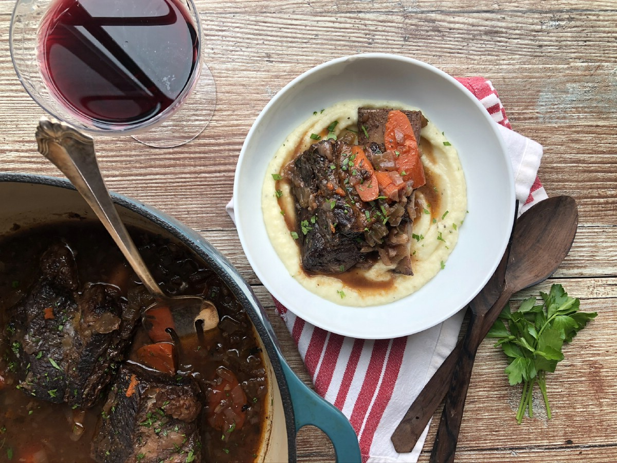 Short ribs in dutch oven by white bowl