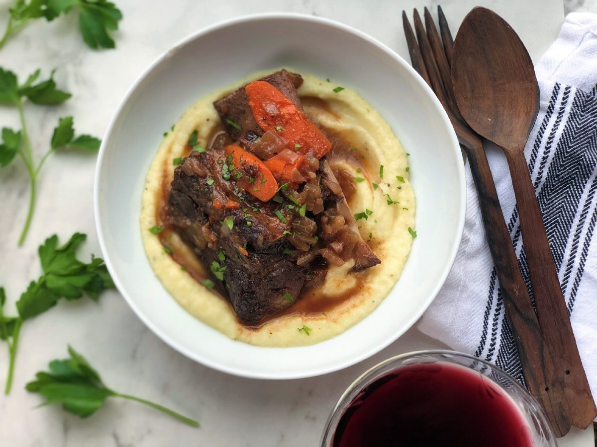 Braised short ribs on parsnip puree in white bowl