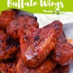 Buffalo chicken wings on white plate with dip