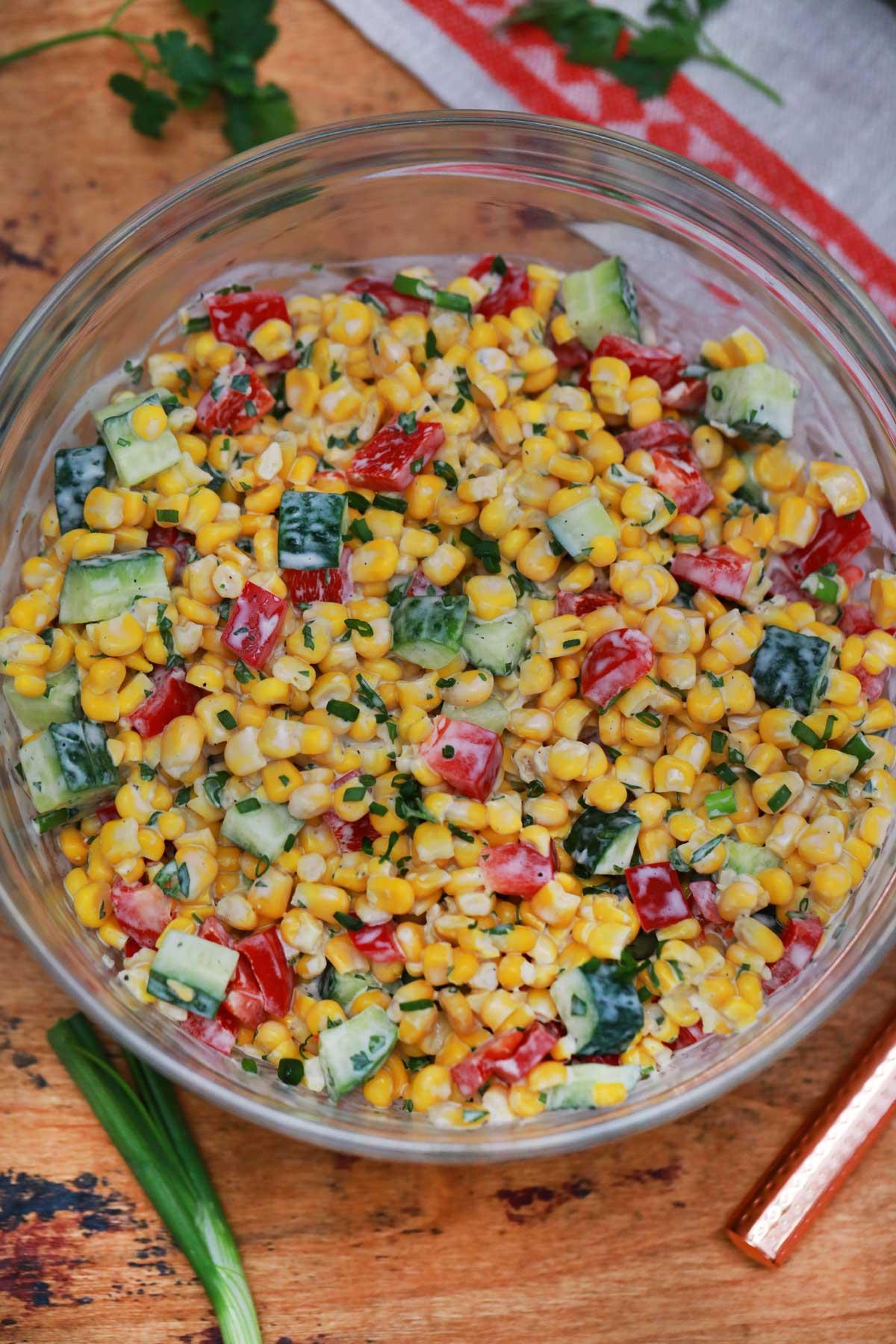 Creamy corn salad in large glass bowl