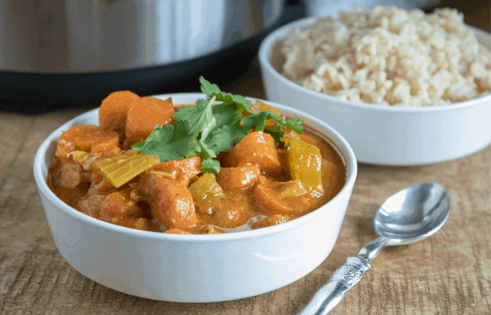 White bowl of curry by pressure cooker