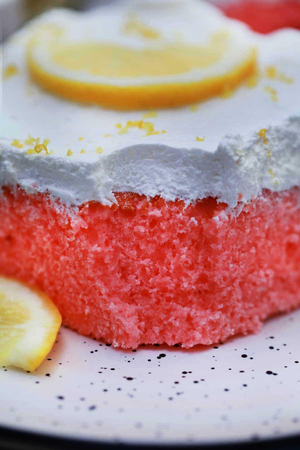 Slice of pink lemonade cake on white plate