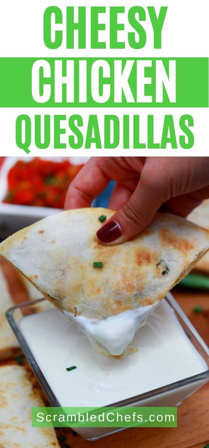 Hand dipping quesadilla in sour cream